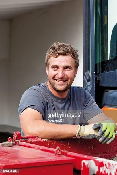 Germany, Rhineland Palatinate, Young man looking away, smiling