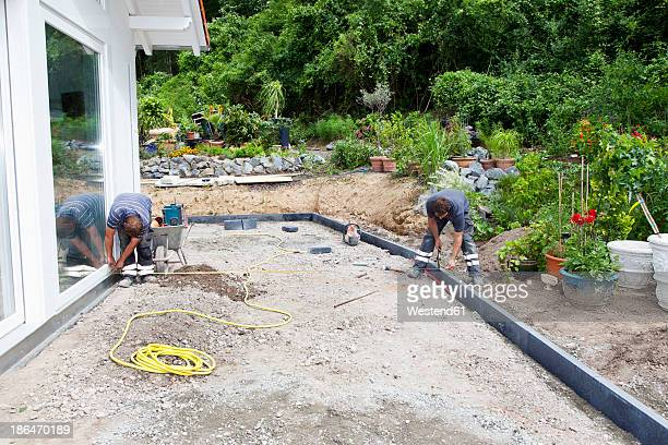 Germany,  Rhineland Palatinate, Young men working at construction site