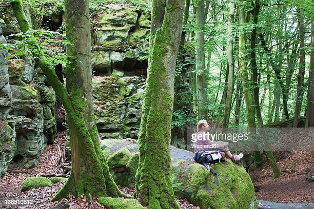 Germany, Rhineland-Palatinate, Eifel Region, South Eifel Nature Park, View of woman hiker sitting on bunter rock formations at beech tree forest