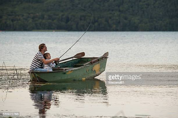 Germany, Rhineland-Palatinate, Laacher See, father and son fishing from boat