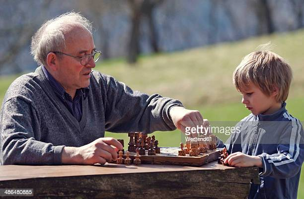 Germany, Rhineland-Palatinate, Leutesdorf, grandfather and grandson playing chess
