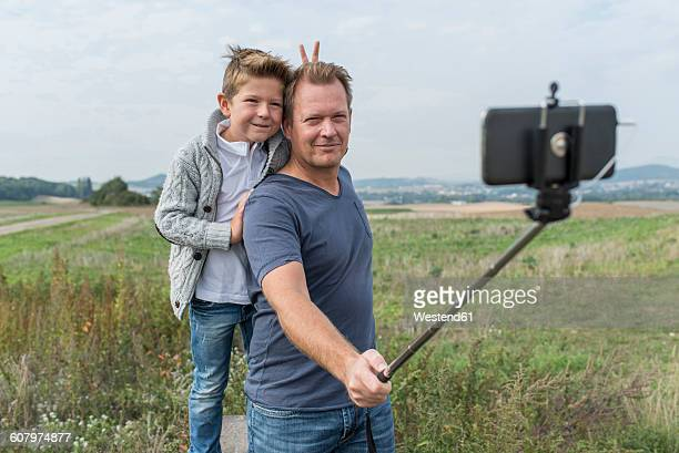 Germany, Rhineland-Palatinate, portrait of father and little son taking a photo with selfie stick in nature