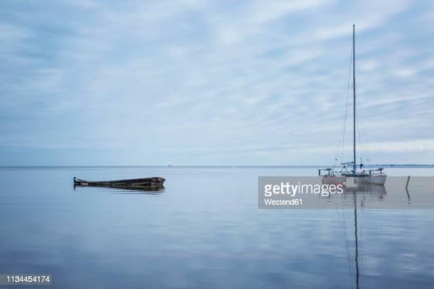 Germany, Ruegen, Putbus, Lauterbach, catamaran and boat wreck on the Baltic Sea