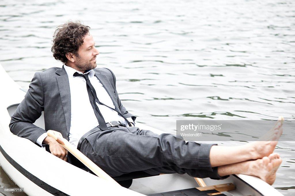 Germany, Rur Reservoir, businessman relaxing in canoe : Stock-Foto