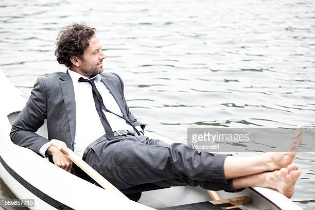 germany, rur reservoir, businessman relaxing in canoe - mid adult men stock-fotos und bilder