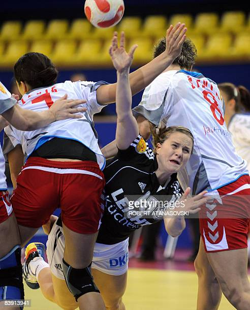 Germany' s Anna Loerper vies with Serbia's Dijana Stevin and Andrea Lekic during the 8th Women's Handball European Championships match on December 4...
