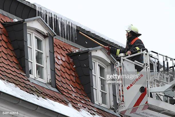 Germany Saarland Saarbruecken firebrigade is removing icicles from a roof