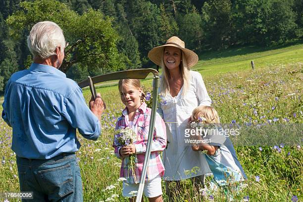 Germany, Salzburg, Farmer and family in summer meadow, smiling