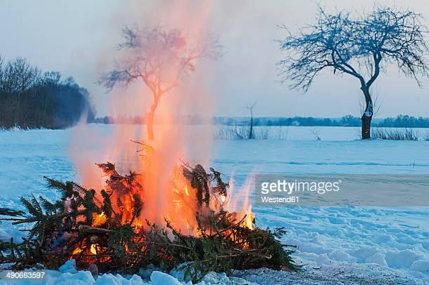 Germany, Saxony, camp fire at winter landscape