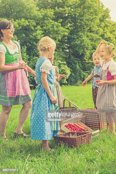germany, saxony, children and their educator in traditonal clothes on a meadow - school cane stock photos and pictures