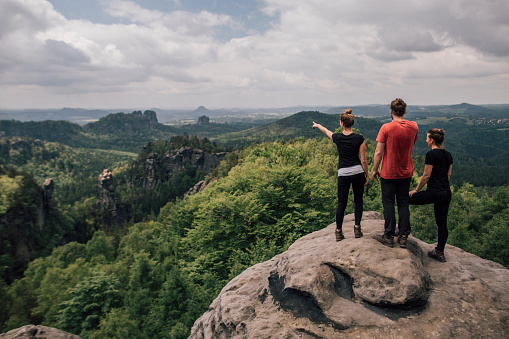 Germany, Saxony, Elbe Sandstone Mountains, friends on a hiking trip standing on rock - gettyimageskorea