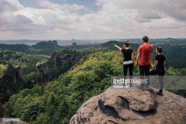 germany, saxony, elbe sandstone mountains, friends on a hiking trip standing on rock - saxony stock pictures, royalty-free photos & images