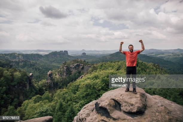 germany, saxony, elbe sandstone mountains, man on a hiking trip standing on rock cheering - エルプサンドシュタイン山地 ストックフォトと画像