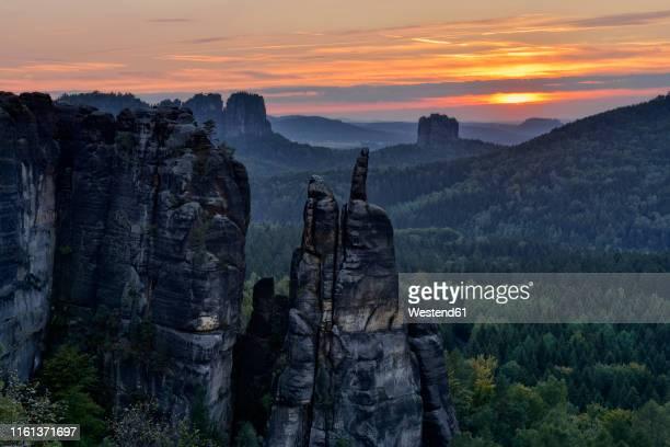 germany, saxony, elbe sandstone mountains, sandstone rock brosinnadel with falkenstein and schrammsteine in background at sunset - felsformation stock-fotos und bilder