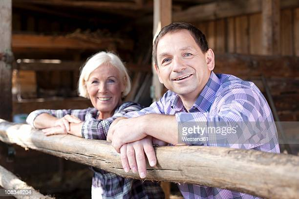 Germany, Saxony, Man and woman in the farm, smiling, portrait