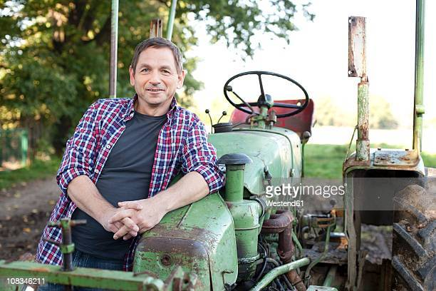 Germany, Saxony, Senior man standing by tractor, smiling