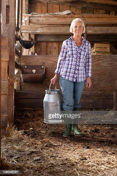 Germany, Saxony, Senior woman holding milk churn in the farm