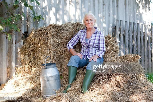 Germany, Saxony, Senior woman sitting on grass with milk churn