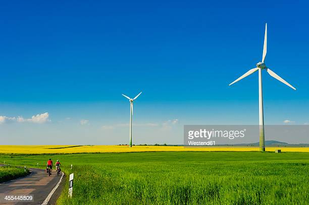 Germany, Saxony, Wind turbines in oilseed rape field