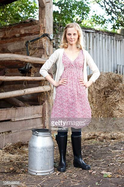 Germany, Saxony, Young woman with milk churn, portrait