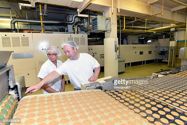 Germany, Saxony-Anhalt, two workers at production line with cookies in a baking factory
