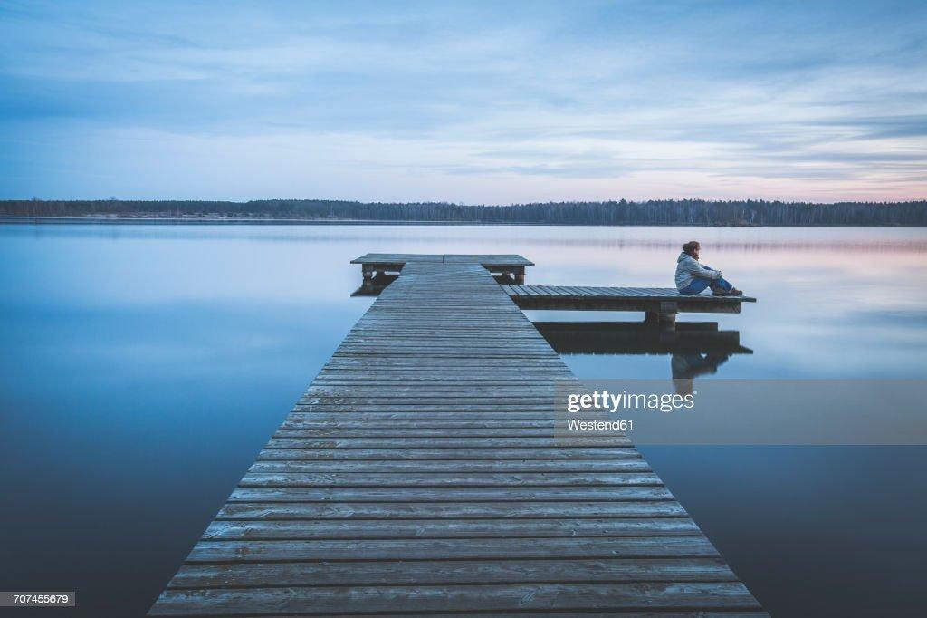 Germany, Saxony-Anhalt, woman sitting on jetty at Lake Bergwitz : Stock Photo