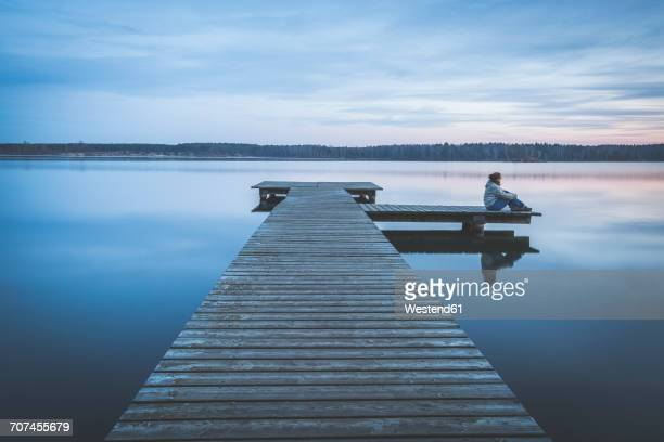 Germany, Saxony-Anhalt, woman sitting on jetty at Lake Bergwitz