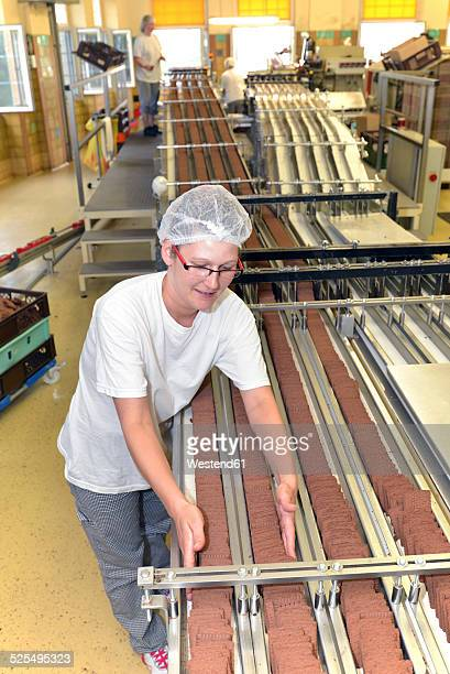 Germany, Saxony-Anhalt, woman working at production line in a baking factory