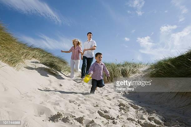 Germany, Schleswig Holstein, Amrum, Boy with parents running on beach
