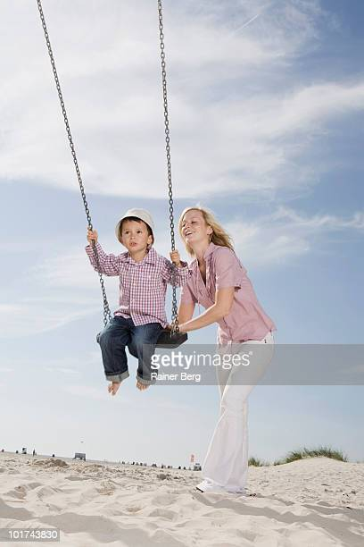 Germany, Schleswig Holstein, Amrum, Mother pushing son (2-3) on swing