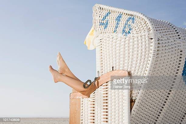 Germany, Schleswig Holstein, Amrum, Young woman relaxing in hooded beach chair, low section