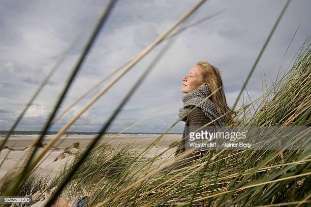 germany, schleswig holstein, amrum, young woman on grassy sand dune, eyes closed - blond frauen strand stock-fotos und bilder