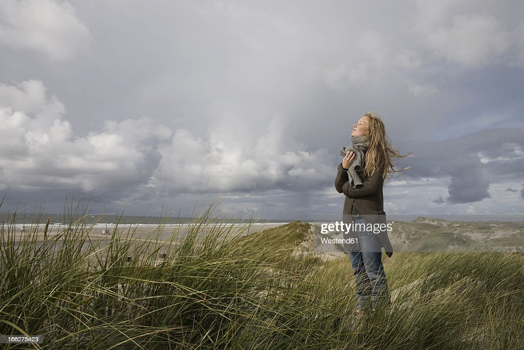 Germany, Schleswig Holstein, Amrum, Young woman on grassy sand dune : Stock-Foto