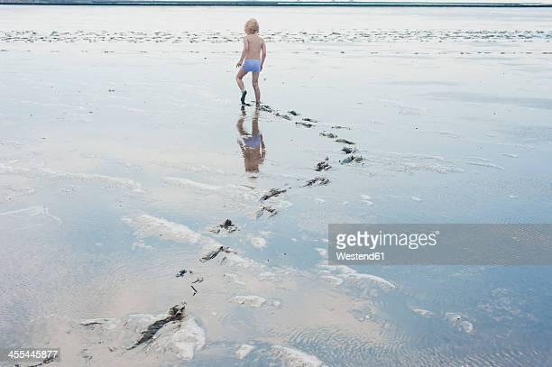 Germany, Schleswig Holstein, Boy playing in mud at beach