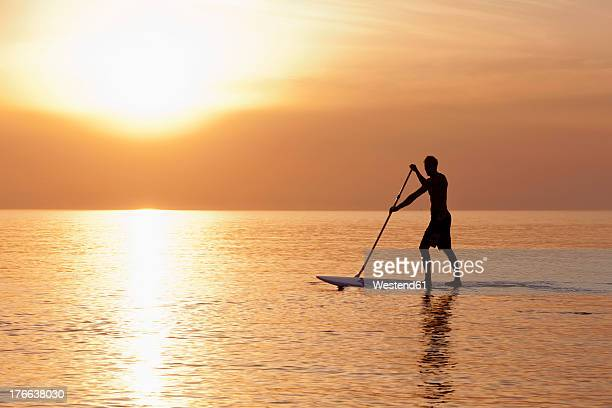 Germany, Schleswig Holstein, Man on stand up paddle board on Baltic sea