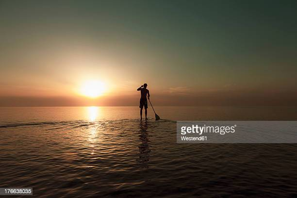 Germany, Schleswig Holstein, Man stand up paddle board on Baltic sea