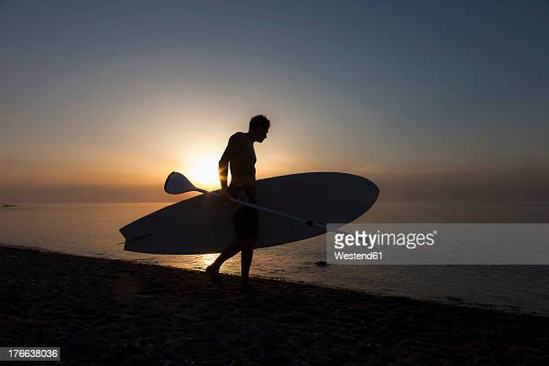 Germany, Schleswig Holstein, Man with stand up paddle board at Baltic Sea