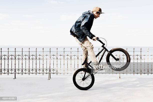 germany, schleswig holstein, teenage boy jumping with bmx bike - stunt stock photos and pictures