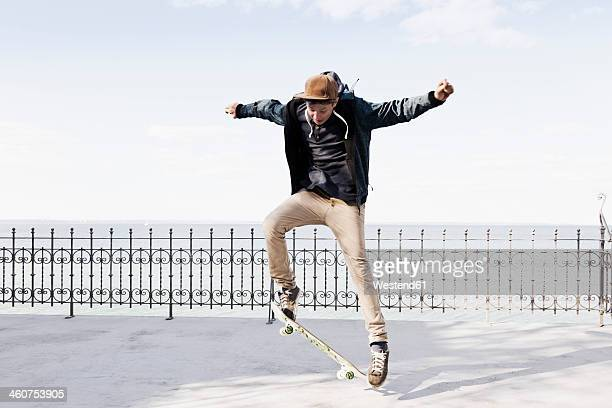 Germany, Schleswig Holstein, Teenage boy jumping with skateboard