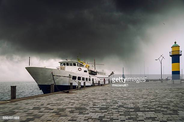Germany, Schleswig-Holstein, Eckernfoerde, cruise vessel at port, dark cloud