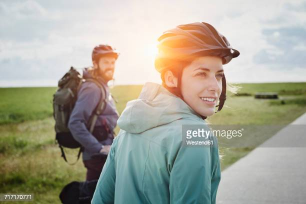 Germany, Schleswig-Holstein, Eiderstedt, couple on a bicycle tour having a break in marsh landscape