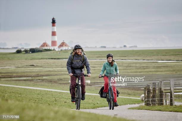 Germany, Schleswig-Holstein, Eiderstedt, couple riding bicycle near Westerheversand Lighthouse