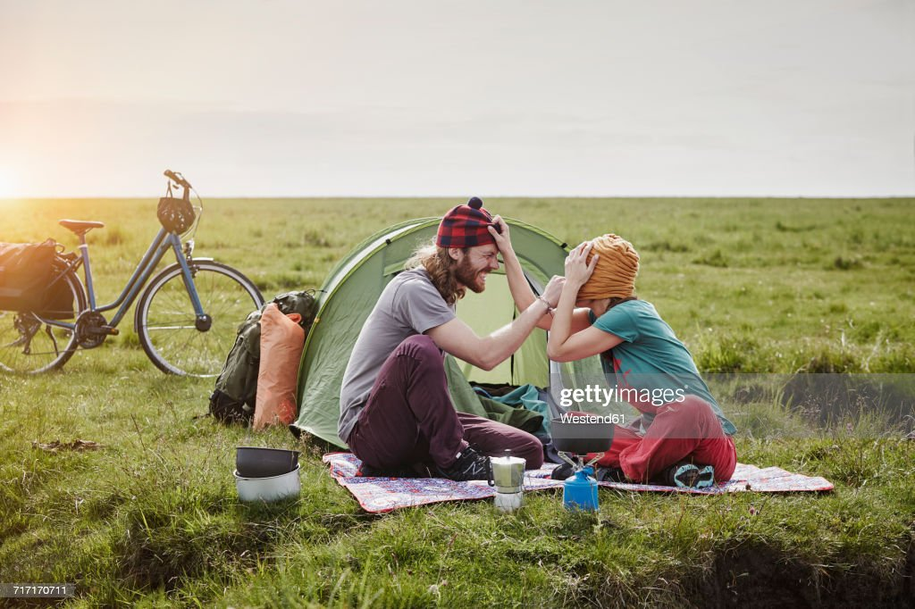 Germany, Schleswig-Holstein, Eiderstedt, playful couple with bicycles camping in marsh landscape : Stock-Foto