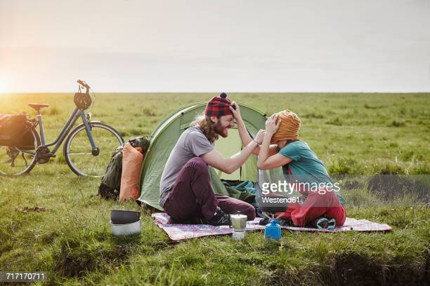 Germany, Schleswig-Holstein, Eiderstedt, playful couple with bicycles camping in marsh landscape