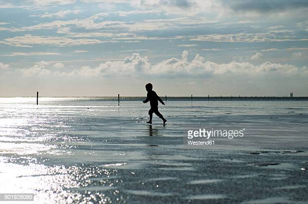 Germany, Schleswig-Holstein, Sankt Peter-Ording, North Sea, boy running at beach