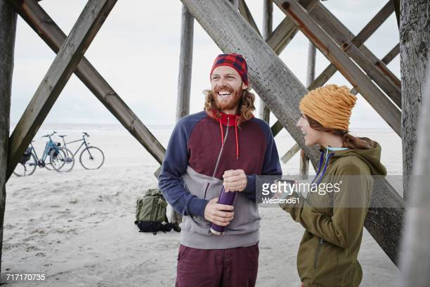 germany, schleswig-holstein, st peter-ording, couple on a bicycle trip having a break on the beach - sankt peter ording stock-fotos und bilder