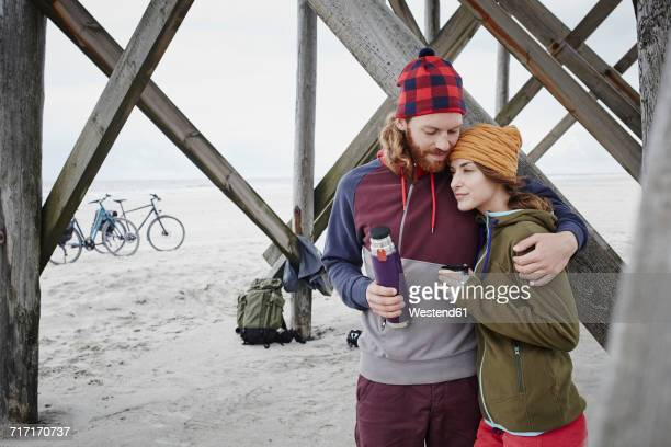 Germany, Schleswig-Holstein, St Peter-Ording, couple on a bicycle trip having a break on the beach