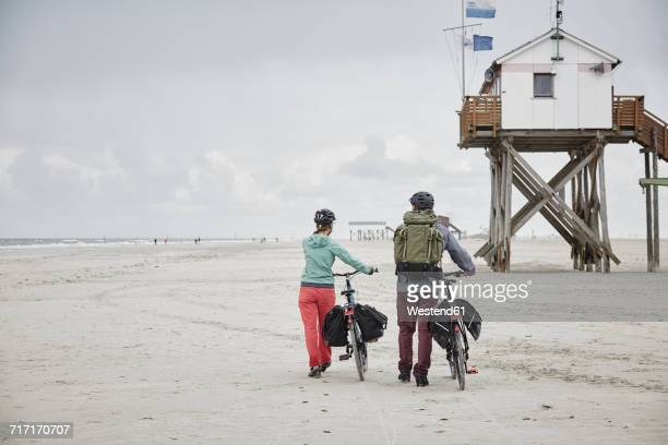 Germany, Schleswig-Holstein, St Peter-Ording, couple pushing bicycles on the beach
