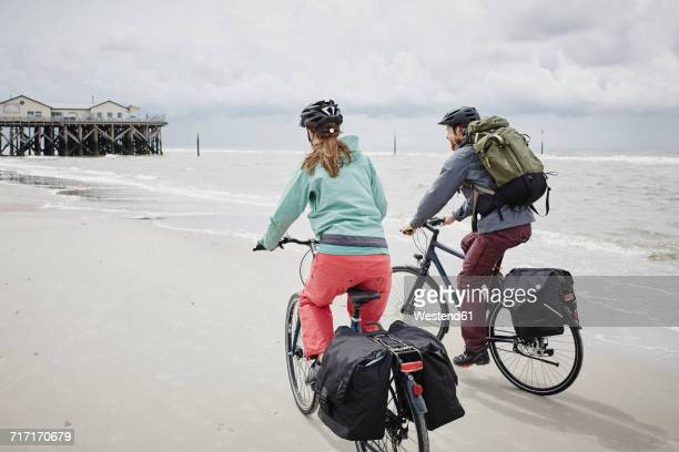 Germany, Schleswig-Holstein, St Peter-Ording, couple riding bicycle on the beach