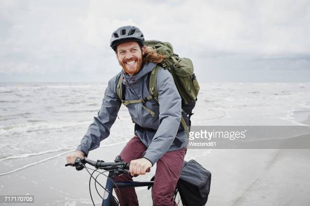 Germany, Schleswig-Holstein, St Peter-Ording, happy young man riding bicycle on the beach